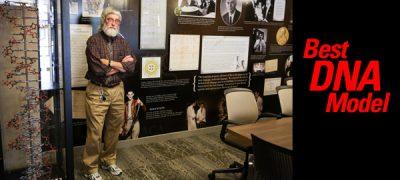 Retired teacher Roscoe Stribling standing beside DNA model in room dedicated to Marshall Nirenberg, Nobel Prize 1968